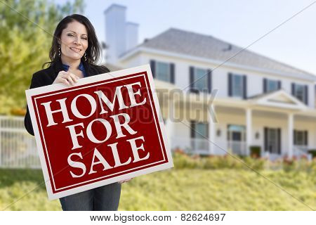 Smiling Hispanic Female Holding Sold For Sale Sign In Front of Beautiful House.