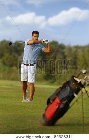Young male golfer swinging golf club, following golf ball.