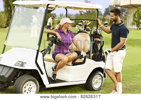 Golfers flirting in the fairway in golf cart, smiling.