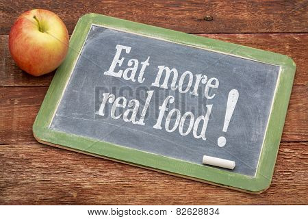 Eat more real food  - text on a slate blackboard against red barn wood with a n apple