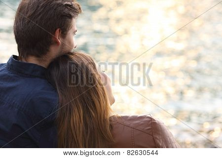 Couple Hugging And Watching Sunset On The Beach