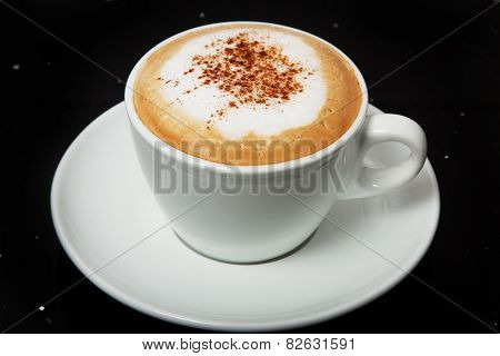 Cappuccino with cinnamon in a white cup.