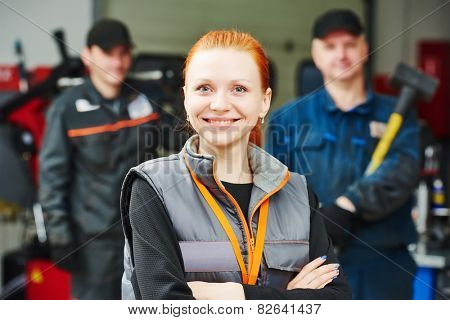 Portrait of female repairman auto mechanic in car auto repair or maintenance shop service station
