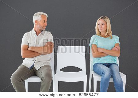 Unhappy couple not speaking to each other against grey poster