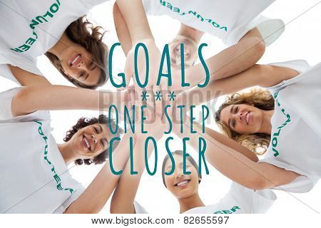 Cheerful group of volunteers putting hands together against goals one step closer
