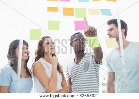 Cheerful teamwork pointing sticky notes and interacting in this office poster