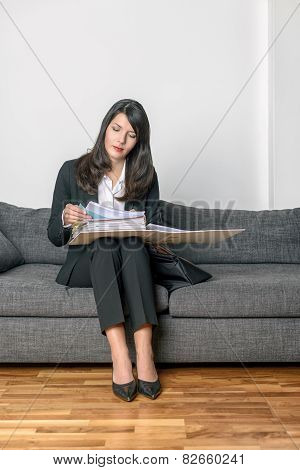 Young Businesswoman Sitting Reading Her Notes