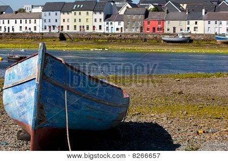 Blue Boat With The Houses In The Background