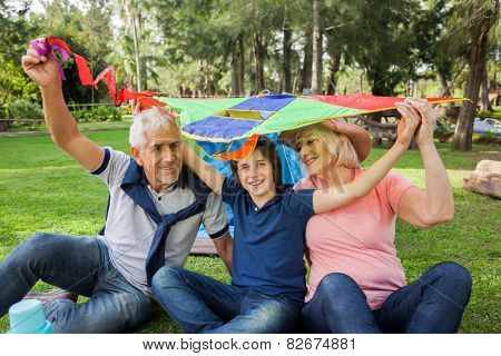 Portrait of happy boy with grandparents holding kite over heads at campsite