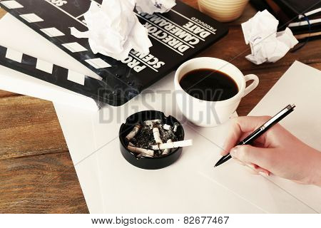 Female hand with cup of coffee, moving clapper and sheets of paper on wooden background