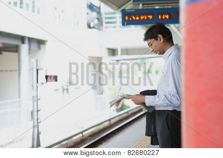 Candid Asian Indian businessman waiting at public train station, standing and reading on newspaper.