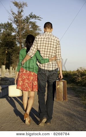 Couple Walking With Luggage In Hand