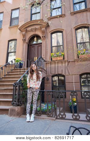 Young woman walking near old houses in historic district of West Village