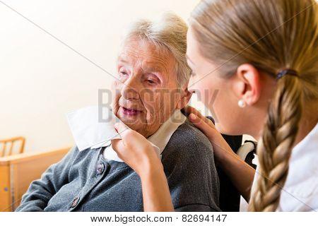 Nurse wiping mouth of elderly senior woman in nursing home