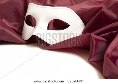 White theatrical mask and red silk fabric on a white background
