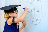 Cute little student girl in academic hat during the lesson at school. Educational concept. poster
