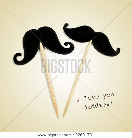 the text I love you daddies and two moustaches glued to wooden toothpicks on a beige background