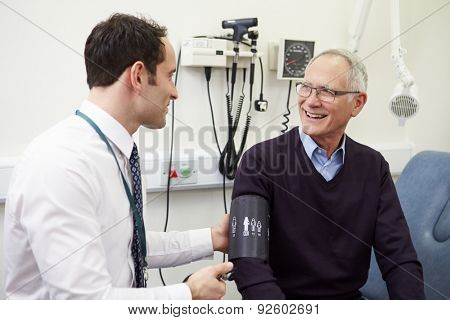 Doctor Taking Senior Patient's Blood Pressure In Hospital