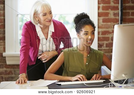 Two Women Working At Computer In Contemporary Office