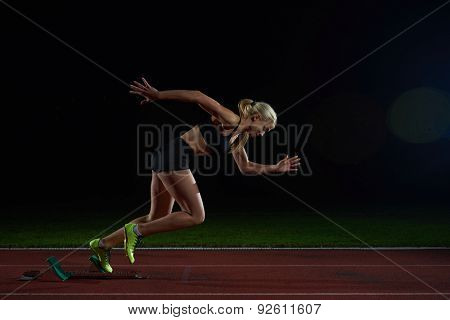 woman  sprinter leaving starting blocks on the athletic  track. Side view. exploding start