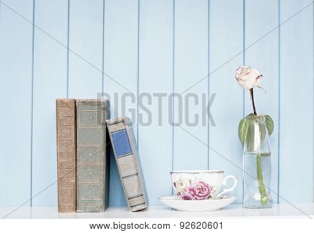 Old Books, China Cup And Rose In The Bottle On Bookshelf
