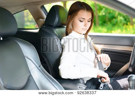 In safety. Young beautiful woman sitting in car and fastening seat belt poster