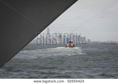 STATEN ISLAND, NY - MAY 20 2015: Harbor tug Ellen McAllister heads toward Lower Manhattan after helping a Navy ship dock at Sullivans Pier in Staten Island at the beginning of Fleet Week in New York.