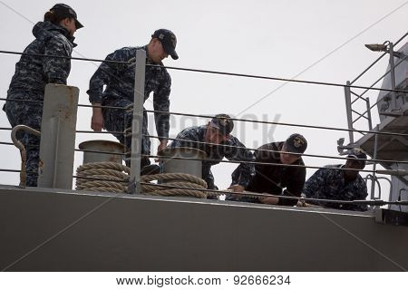 STATEN ISLAND, NY - MAY 20 2015: Linesmen work on the USS Barry (DDG 52) guided-missile destroyer while mooring for Fleet Week NY at Sullivans Pier.