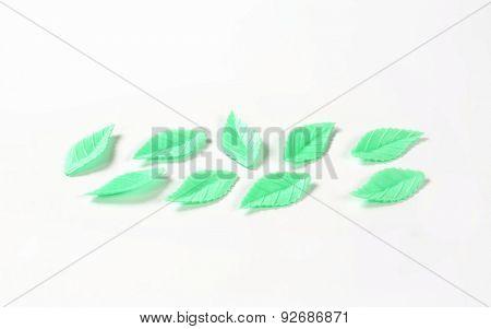 green sugar leaves - eatable cake decoration on white background