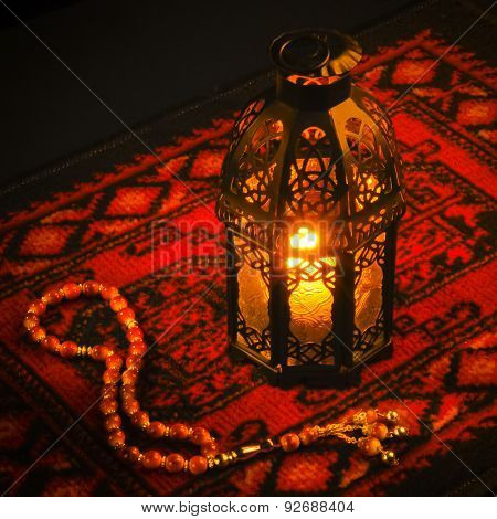 Ramadan greeting card background. An illuminated lamp on bright red carpet background.