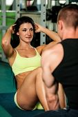 Fitness couple workout - bikini fitness woman works abs poster