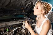 Girl checks the oil level with dipstick in their own broken car poster
