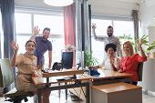 business, startup and office concept - happy creative team waving hands in office poster