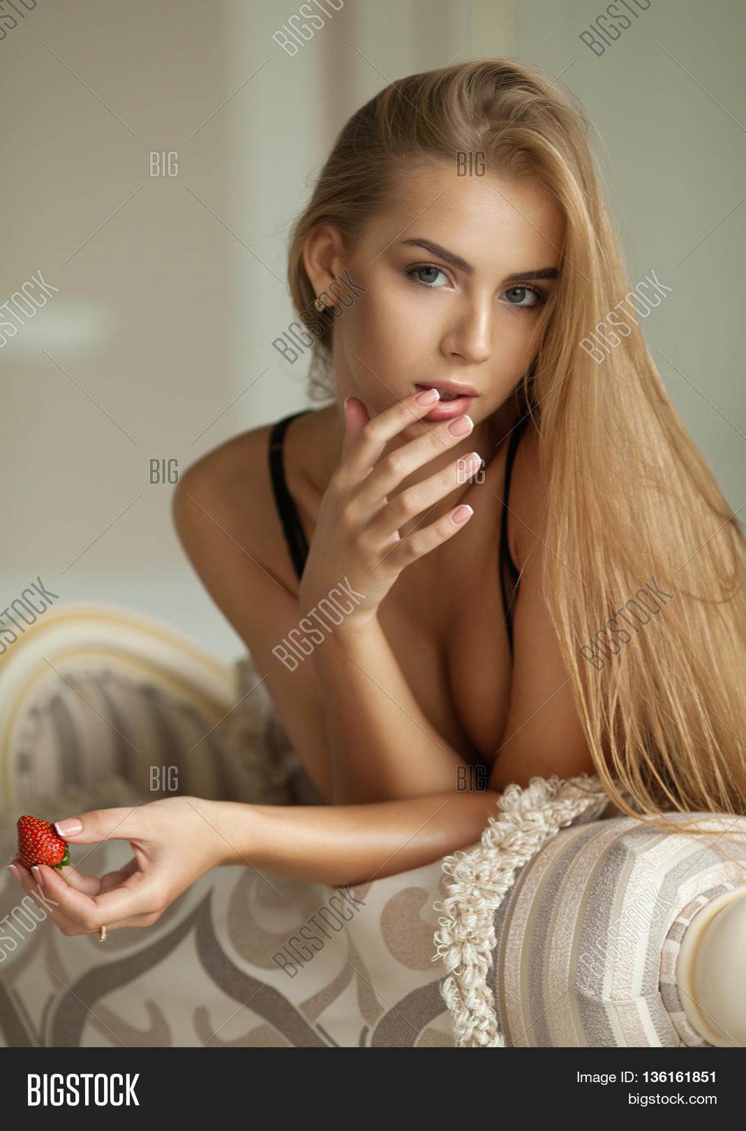 50ee8b69f5 Beautiful and sexy young blonde woman lying on bed eating strawberries