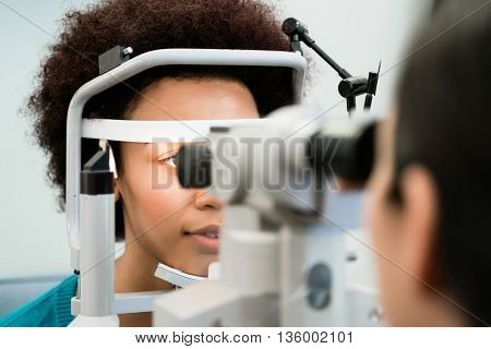 Woman having eyes measured with refractometer at optician or ophthalmologist