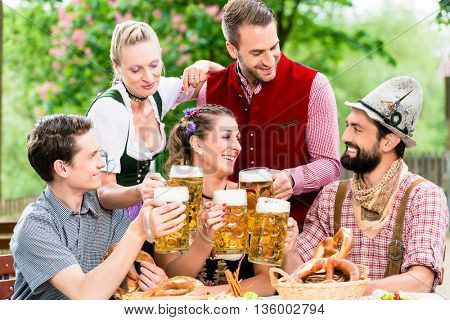 In Beer garden - friends in Tracht, Dirndl and Lederhosen drinking a fresh beer in Bavaria, Munich, Germany