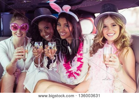 Frivolous women drinking champagne in a limousine on a night out