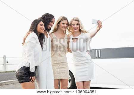 Well dressed women taking a selfie next to a limousine on a night out