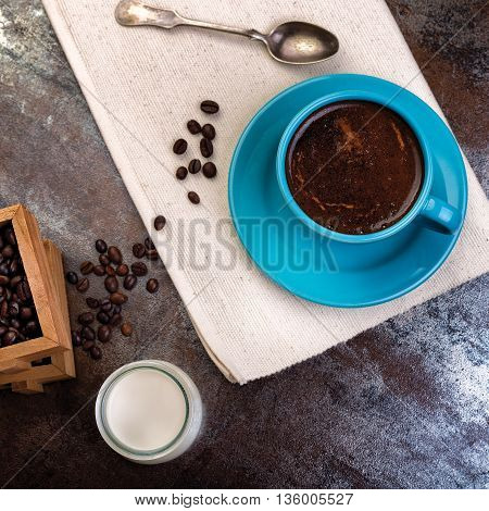 Cup of coffee and wooden containers filled with cofee beans on the rust background. Cane sugar. Low light.