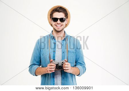 Portrait of smiling young man in hat and sunglasses using old vintage photo camera over white background