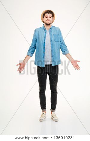 Confused cute young man in jeans shirt standing and shrugging over white background