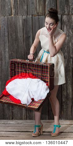 beautiful girl in white dress dropped suitcase with his clothes