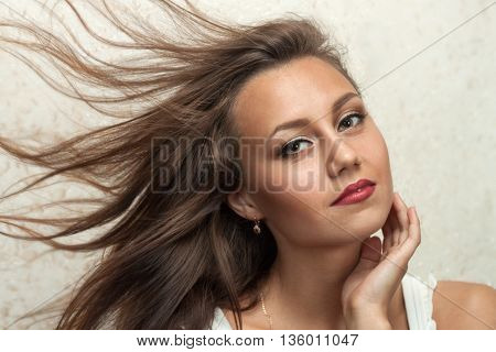 Portrait of beautiful girl with clean face and flying hair closeup