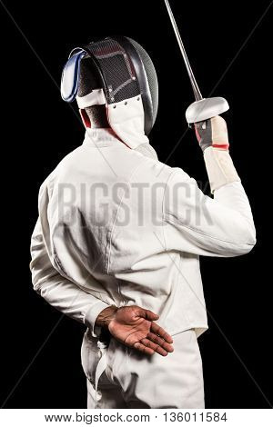 Rear view of man wearing fencing suit practicing with sword on black background