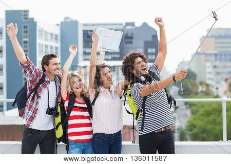 Group of friends taking selfie with selfie stick on terrace