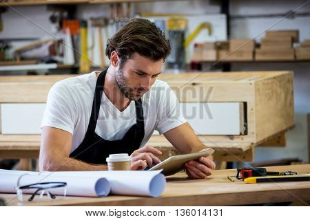 carpenter is using his tablet in a dusty workshop
