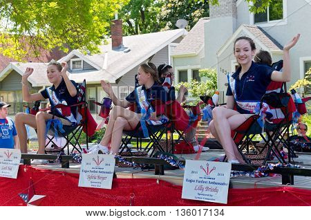 WEST ST. PAUL, MINNESOTA - MAY 21, 2016: Ambassadors for City of Eagan Funfest wave to crowd at annual West St. Paul Days Grande Parade on May 21.