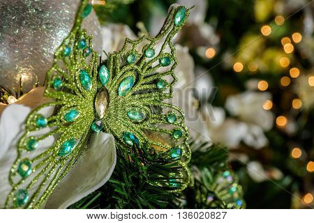Butterfly Christmas ornament featuring artificial jewels or studs. The background is blurred to show specular highlights (bokeh).