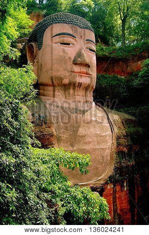 Leshan China - April 25 2005: Begun in 713 A. D. the giant Buddha of Leshan carved into a riverside cliff stands 71 meters high