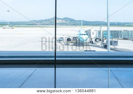 airplane on airfield through glass window
